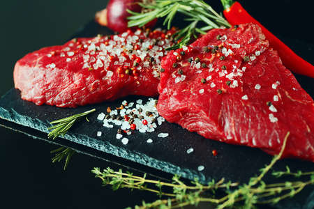 pieces of fresh beef meat abundantly sprinkled with salt, pepper and herbs, lie on a dark background, close-up Stock Photo