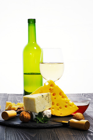 Varieties of cheeses and honey with a glass of white wine on a dark wooden table. Stock Photo