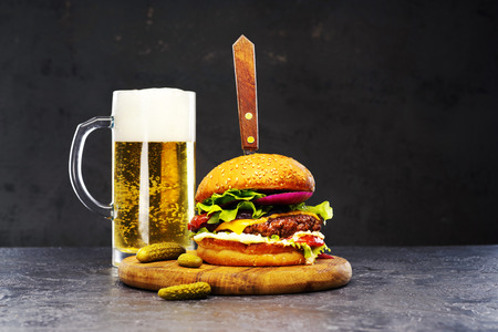 Delicious beef burger with a glass of beer on the board with cheese, vegetables and lettuce, hand made, according to a classic recipe . Archivio Fotografico