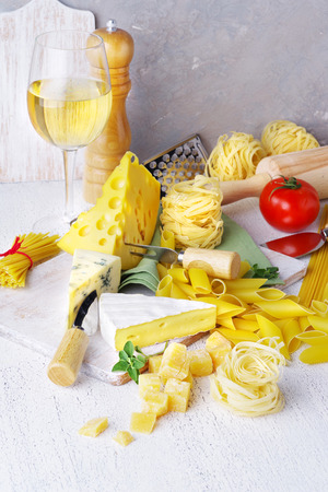 Varied types of pasta and cheeses, tomatoes and ingredients for cooking on a light rustic background.