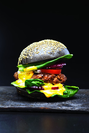 Black beef burger with flowing melted cheese  on a burnt blackboard  on a black background.