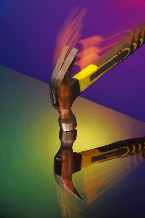 A vintage hammer hits the glass, a reflection in the glass, a colored background. impact resistant glass