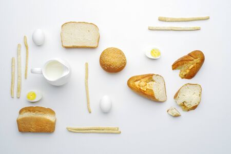 Bread, milk and eggs top view on a white background. Flat lay. Stock Photo