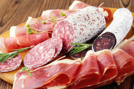 A variety of delicious slices of deli meats, ham and Italian sausage with mold on a wooden board. Фото со стока