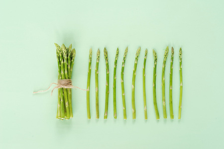 A bunch of young asparagus on a light green background. 스톡 콘텐츠