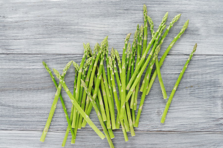 A bunch of young asparagus on wooden background.