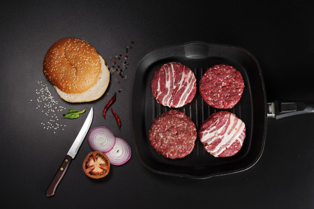 Cutlets for burgers in a grill pan and other ingredients for cooking on a black background, top view.
