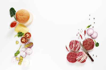 Top view on burgers cutlets and different ingredients for cooking on a white background with space for text.