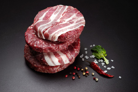 Raw bacon patties for burgers with spices on a black background. Close-up. 스톡 콘텐츠