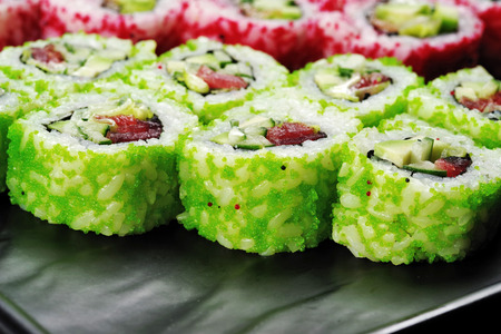 Bright green sushi decorated with flying fish roe, closeup on a black dish. 스톡 콘텐츠
