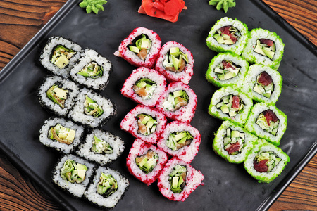 Multi-colored sushi on a black dish, top view.