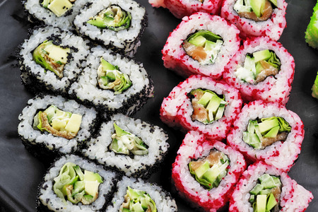 Multi-colored sushi on a black dish, top view, close-up.