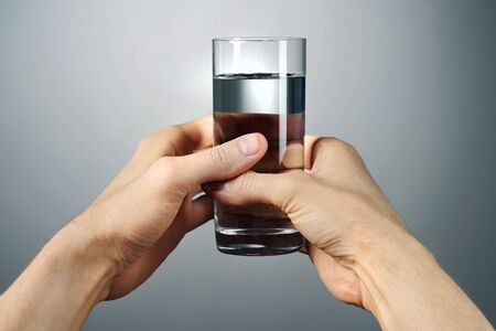 A glass of pure water, which prtyagryat beautiful male hands on a gray background, from the first person. 스톡 콘텐츠
