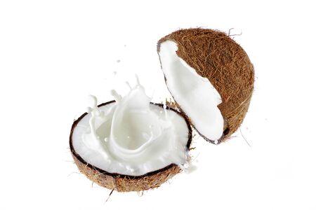 Coconut broken in half. A splash of coconut milk.