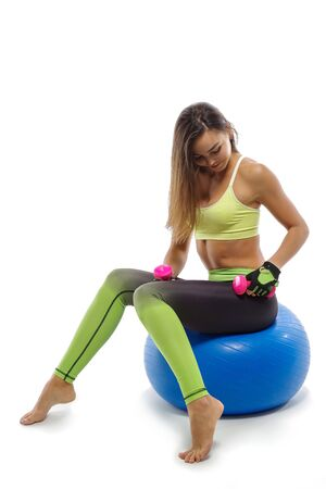 Girl on fitball does exercises with dumbbells, sportswear, white background 스톡 콘텐츠