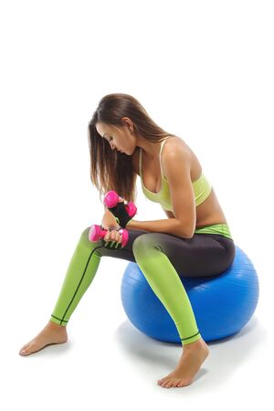 Girl on fitball does exercises with dumbbells, sportswear, white background 免版税图像