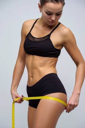 Slender girl in lingerie measures hips, beautiful figure