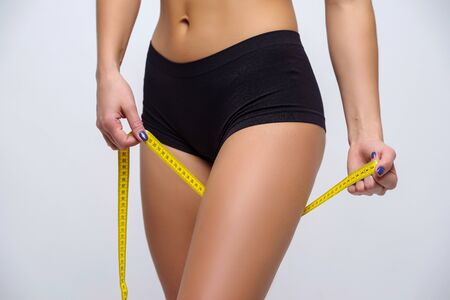 Slender girl in lingerie measures hip, beautiful figure