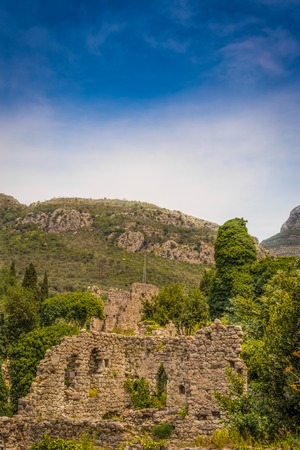 A cloudy evening in the mountains. The completion of the archaeological expedition. Ruins of the ancient city in the mountains in the evening. Foggy view of old stone buildings and streets. Stock Photo