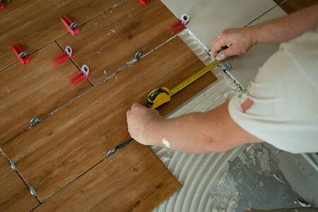 Man putting ceramic tiles on the floor in a residential home. View of a tiler's hands pressing a wood-colored tiles. Finishing a new apartment, renovation and arrangement.