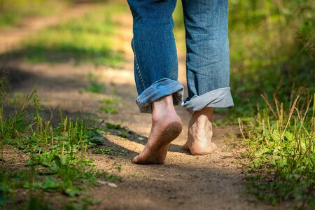 Man walking in park. Close-up of bare feet soiled with ground. healthy lifestyle. Banque d'images