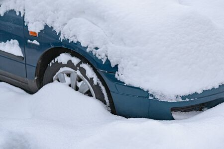 Close up on car standing in the parking lot covered with a thick layer of snow.