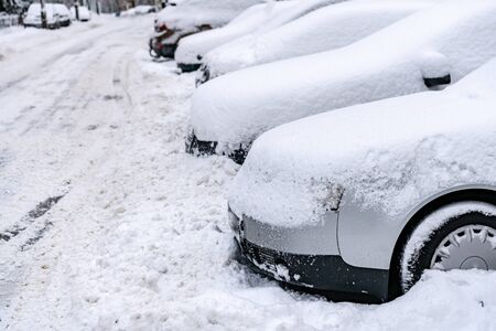 A row of cars standing in the parking lot covered with a thick layer of snow.