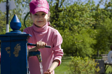 bomba de agua: chica joven que usa la bomba de agua