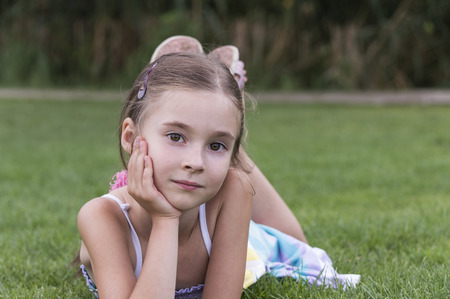 seven persons: portrait of young girl laying and posing in grass