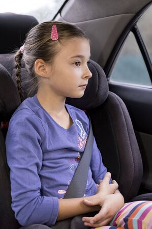 child seat: young girl sitting in child seat in car and looking through window Stock Photo