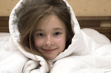 7 8: portrait of posing Caucasian brunette young girl of 7 - 8 years old, laying in bed covered with white blanket over her head