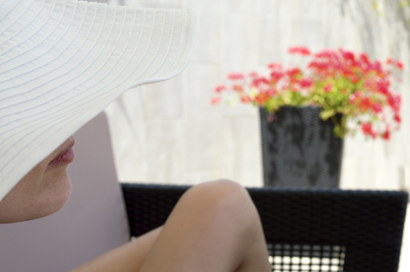 beine spreizen: woman in white hat lying on lounge with legs spread out. Woman face partially covered with hat, mouth and chin visible. Red flower in background