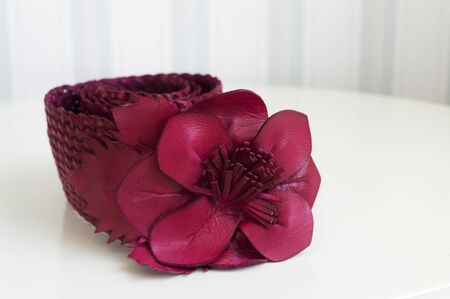 close up of red leather woman waist band with buckle in a form of flower. band lies on white table. Striped blurred wallpapers are seen in background Stock Photo