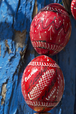 pascha: close up of red painted wooden easter eggs. Eggs are hand made. It is an outdoor shot, eggs are over blue tree bark Stock Photo
