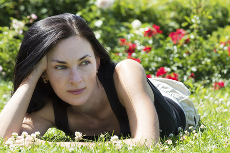 flecks: middle aged woman with flecks of sunlight dressed in black t shirt and shorts lies in background.  Green bushes with red and pink flowers visible in background Stock Photo