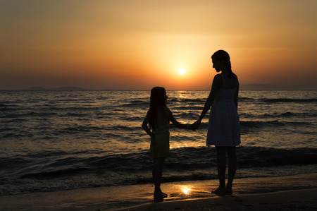 mother and daughter standing on sandy beach with waves breaking around their legs and looking at each other. Only dark silhouettes are visible. Bright red sunset can be seen in the background.