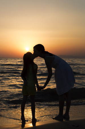 legs around: mother and daughter standing on sandy beach with waves breaking around their legs and kissing. Only dark silhouettes are visible. Bright red sunset can be seen in the background.