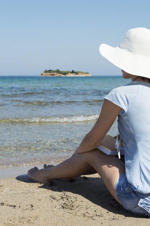 middle aged woman dressed in blue and wearing white hat sits on sandy beach, holds a book and looks far away.  Green island, blue sea and sky visible in background Stock Photo