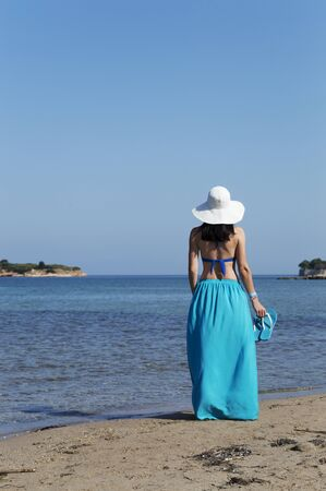 middle aged woman dressed in blue skirt and wearing white hat stands on sandy beach and holds a pair of slippers.  Green trees, rocky coast, blue sea and sky visible in background