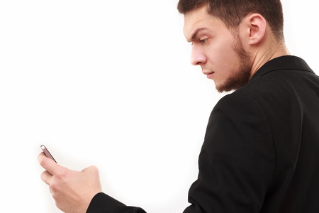eyebrow raised: Businessman with a raised eyebrow using his phone isolated on white Stock Photo