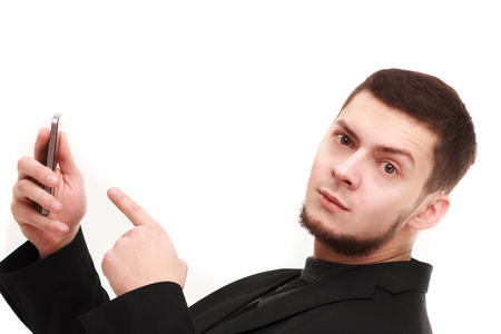 eyebrow raised: Casual businessman pointing with a finger at the phone with a raised eyebrow