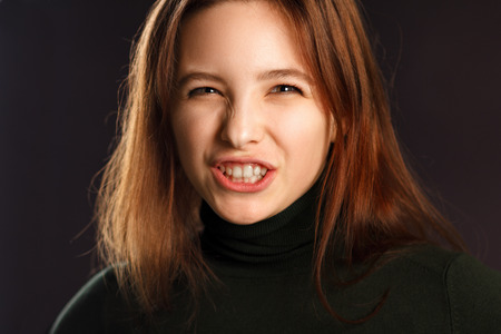 sizzle: Closeup portrait of young woman showing her teeth and hissing Stock Photo