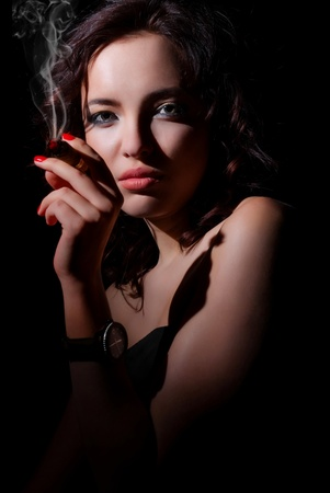 beautiful young girl with a cigar in his hand. Portrait photo