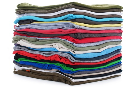 used clothes: pile of colored shirts isolated on white background