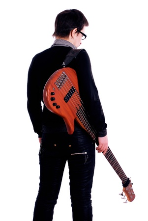 A young boy standing with his back to the bass guitar on a white background