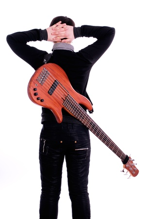 A young boy standing with his back to the bass guitar on a white background photo