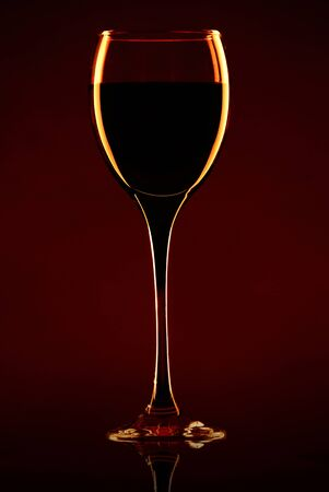 A glass of wine on a dark red background photo
