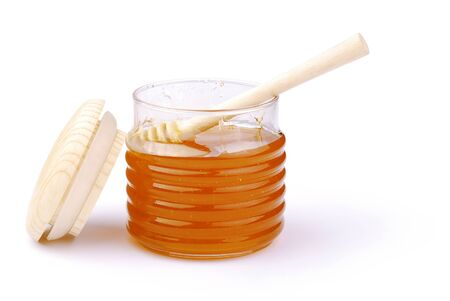 Glass pot of honey on a white background photo