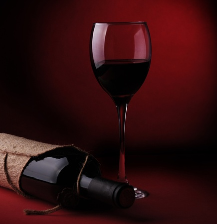 still life of wine bottles and glasses on a dark red background photo