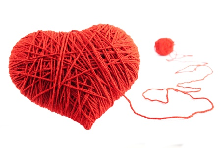 Valentines Day. Red heart shape symbol made from wool isolated on white background
